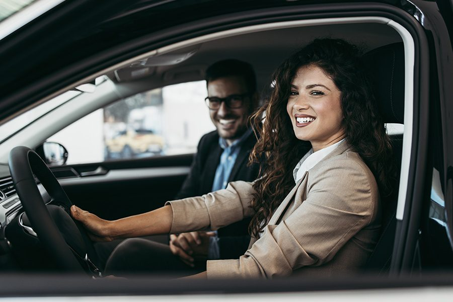 Personal Insurance - Happy Couple Choosing a New Car at a Showroom