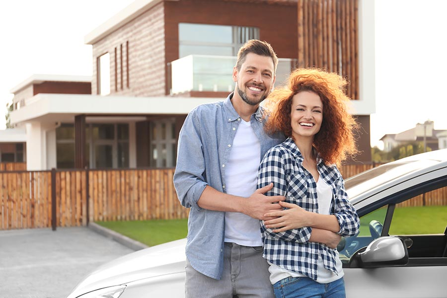 About Our Agency - Couple Pose Outside Their Large Home With Their Silver Car Parked in the Driveway