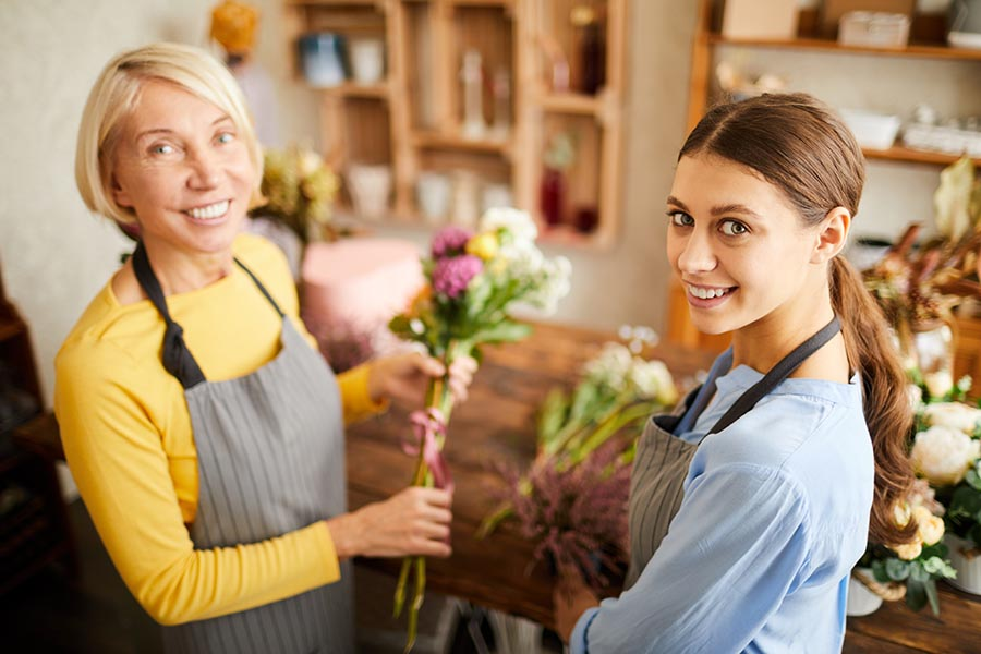Business Insurance - Two Women Running a Flower Shop Hold Showers and Wear Aprons Behind Their Counter