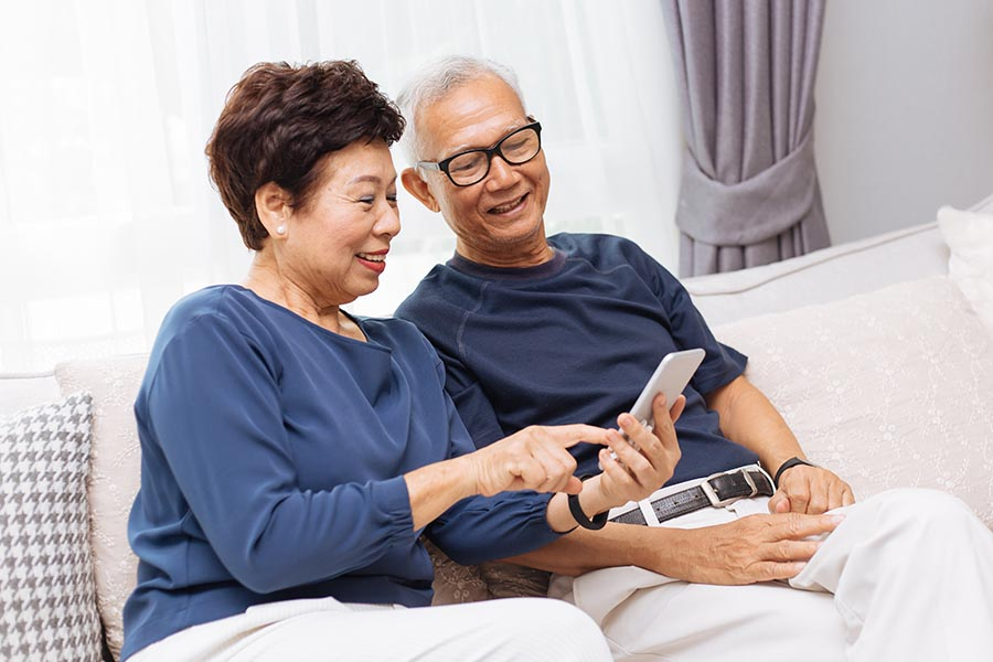 Client Center - Senior Couple Dressed in Blue and White Use a Phone on Their Couch in a Bright Living Room