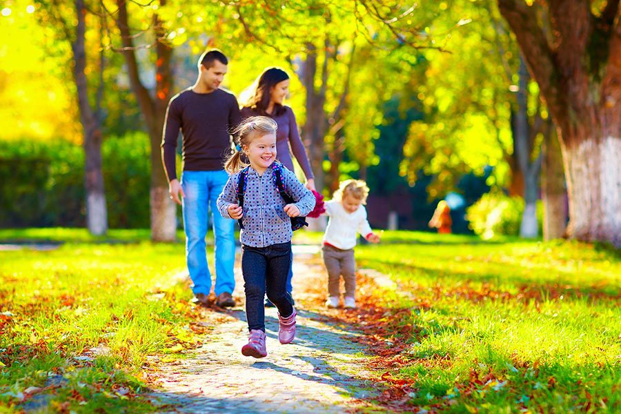 New Lexington, OH Insurance - Family Walks Their Kids Home From School on a Tree-Lined Sidewalk With Leaves Scattered Around