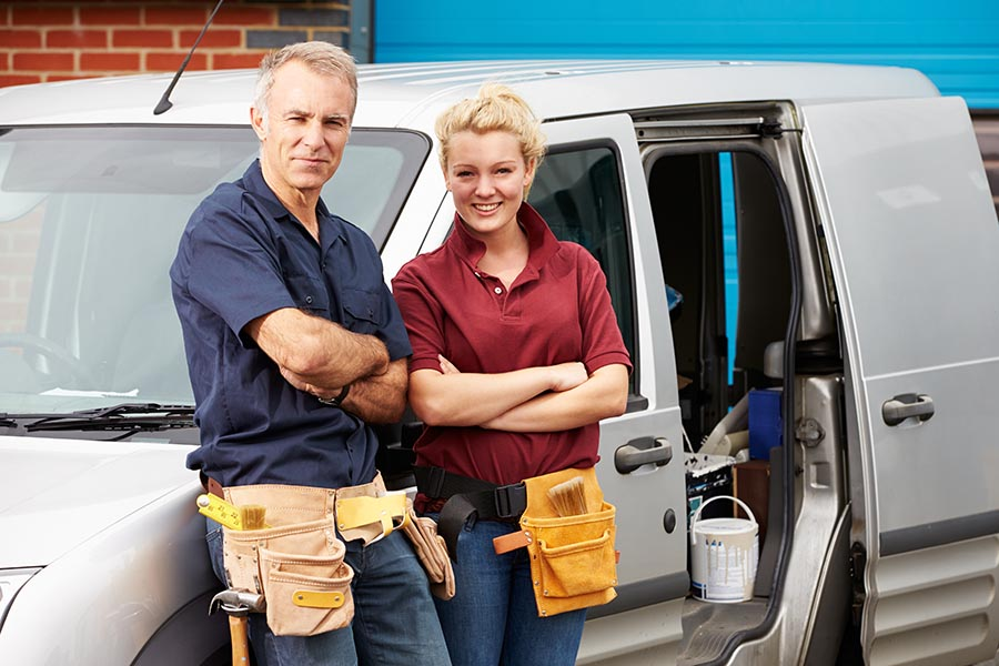 Specialized Business Insurance - Two Contractors Wearing Tool Belts Pose Leaning on Their Gray Service Van, the Door Open Showing Tools and Buckets Inside