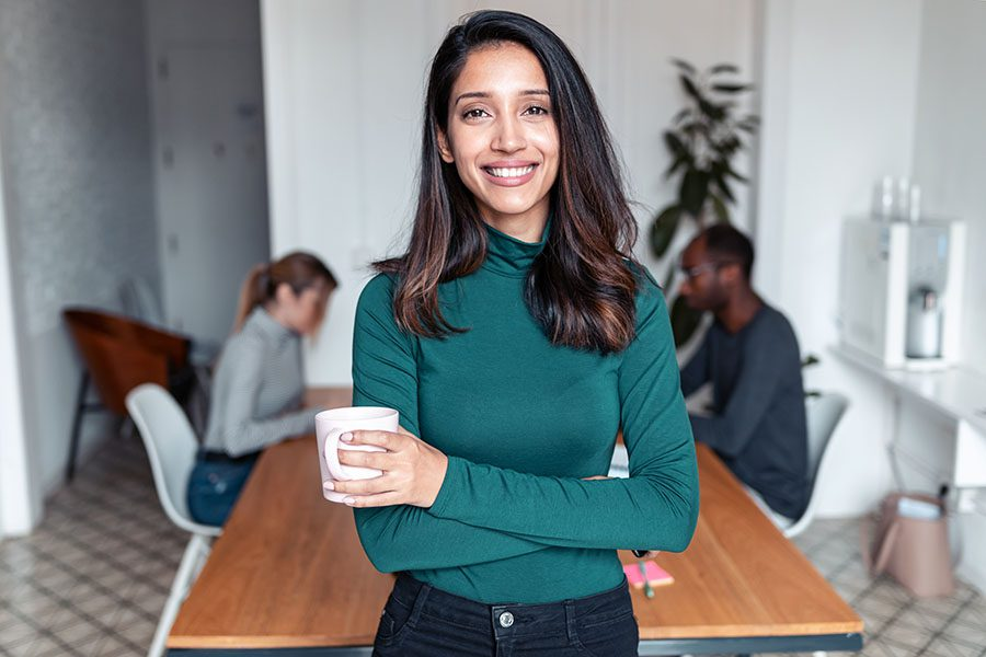 Business Owners Insurance - Portrait of Young Business Woman Standing in the Office with a Cup of Coffee