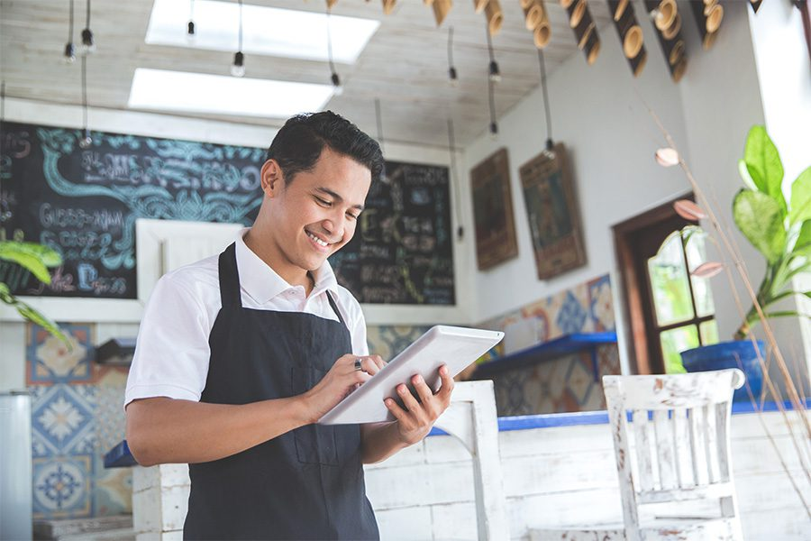 Business Insurance - Business Owner with Apron on Standing with Tablet in Modern Cafe