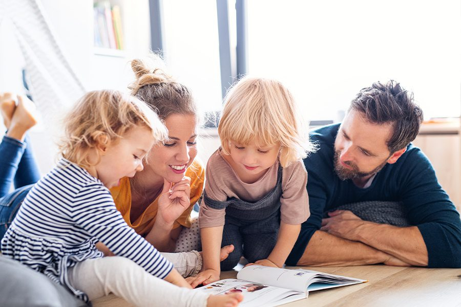 Blog - Young Family with Two Small Children Indoors Reading a Book on the Floor