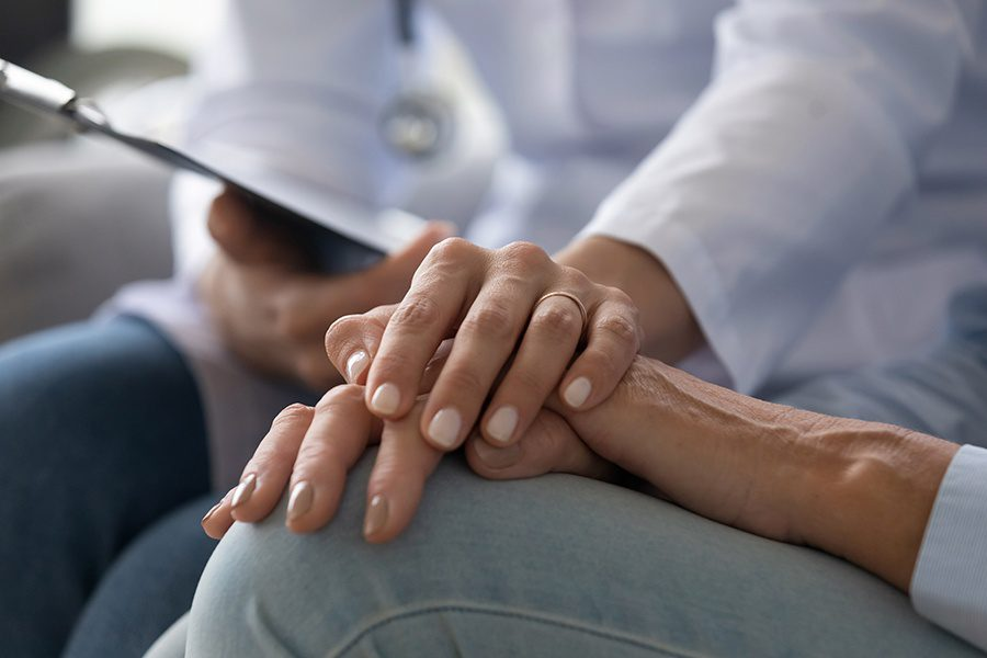 Home Healthcare Insurance - Closeup of Young Woman Doctor Holding Hand of Senior Patient