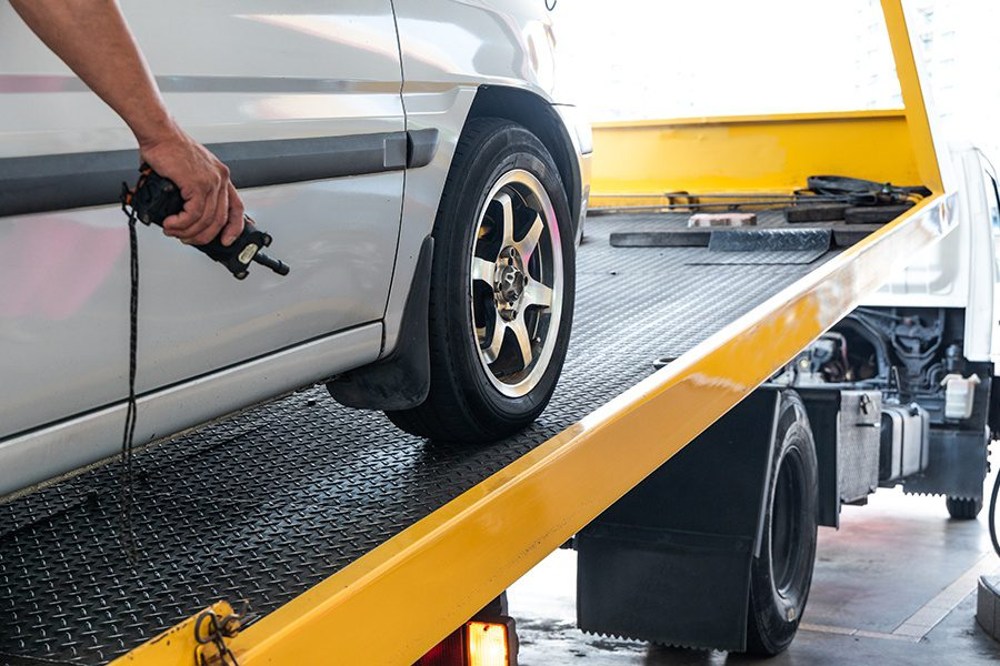 Tow Truck Insurance - Closeup of a Car Being Towed onto Flatbed Tow Truck with Cable