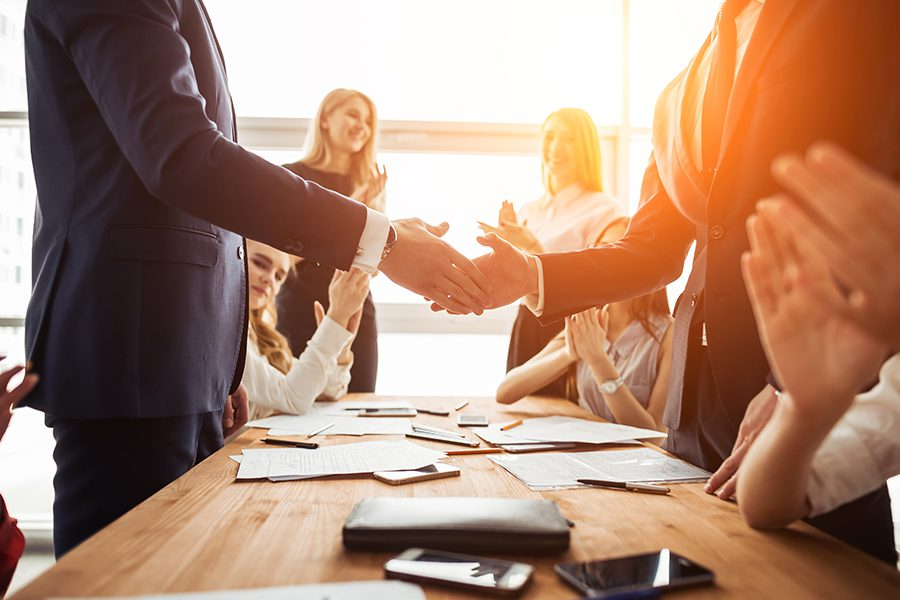 About Our Agency - Bright Lens Flare Shining Through Window Over Businessmen at Integrity Insurance Group Shaking Hands with Fellow Team Members Clapping Along in Agreement