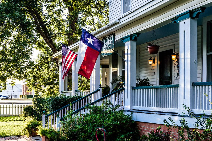 Liberty Hill, TX - Closeup View of Home in Liberty Hill Texas with American and Texas Flags Hanging on Porch