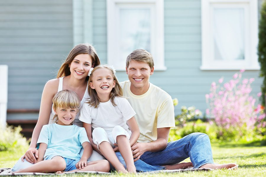 Personal Insurance - Happy Family Posing in Front of House on a Sunny Day While Sitting in the Grass