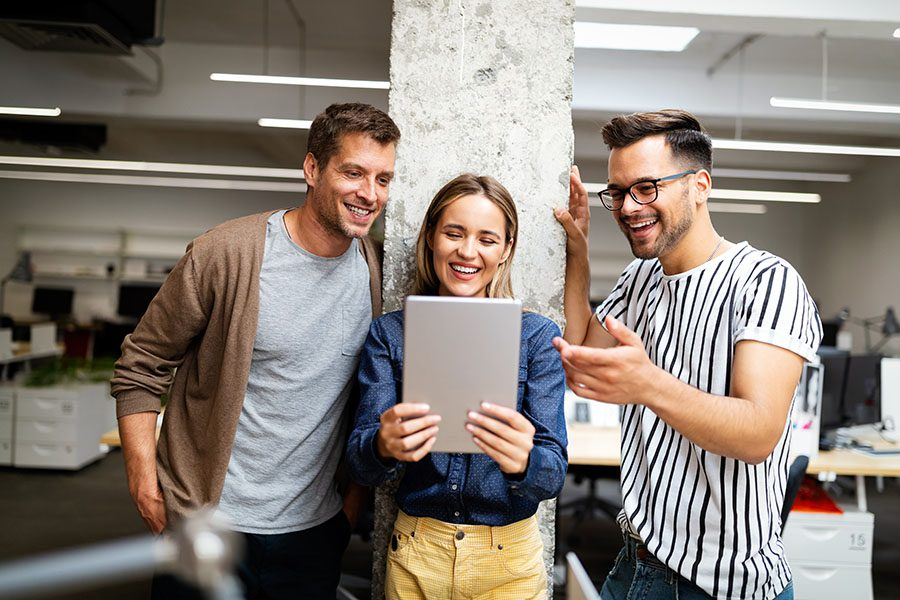 Employee Benefits - Group of Happy Employees in Modern Office Using a Tablet