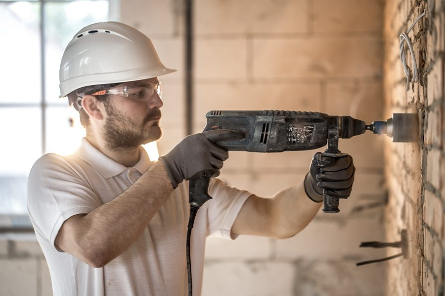 Concrete Pumpers Insurance - Plumber Drilling into Concrete to Gain Access to Pipes
