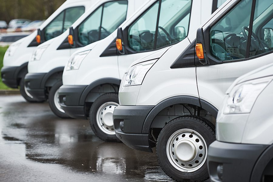 Hard-To-Place Commercial Auto - Closeup View of Multiple Vans of the Same Make and Model Parked In a Line