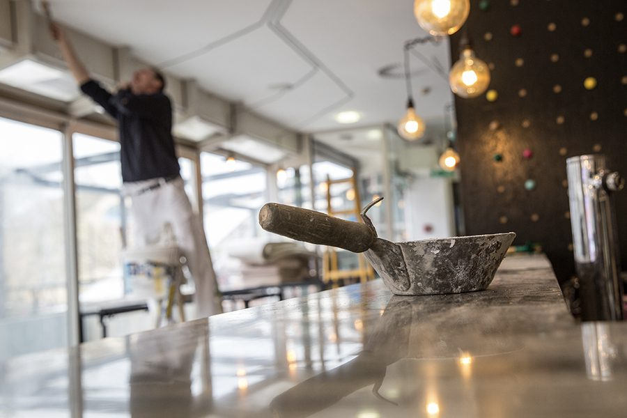 Restoration Contractor Insurance - View of a Construction Worker Fixing and Repairing a Ceiling in a Restaurant With Tools and on a Ladder in the Background and Blurred
