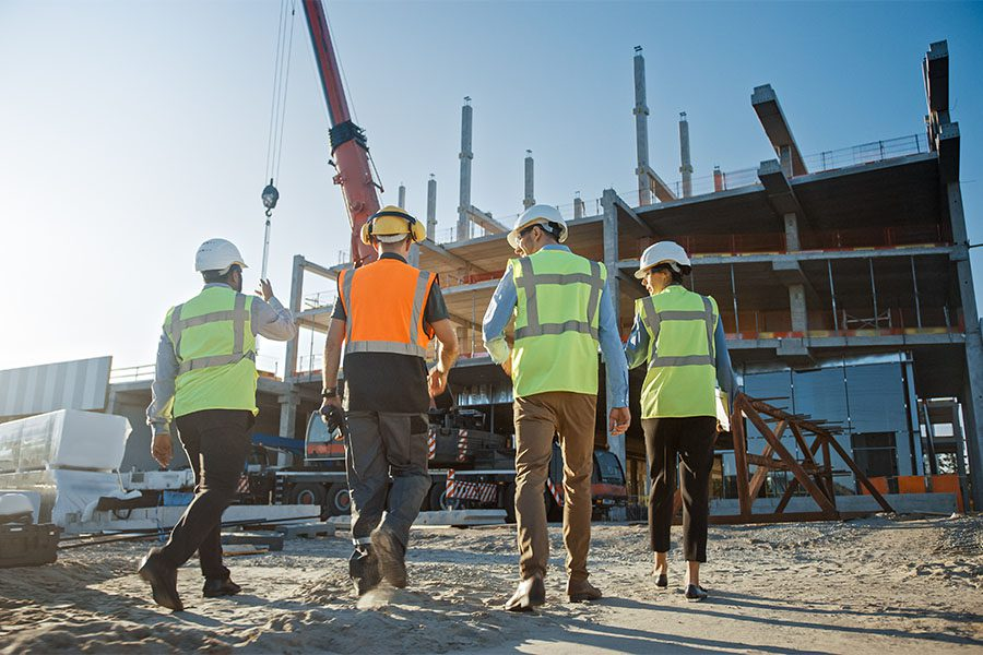 Specialized Business Insurance - View of Group of Contractors and Engineers Working on New Building Construction