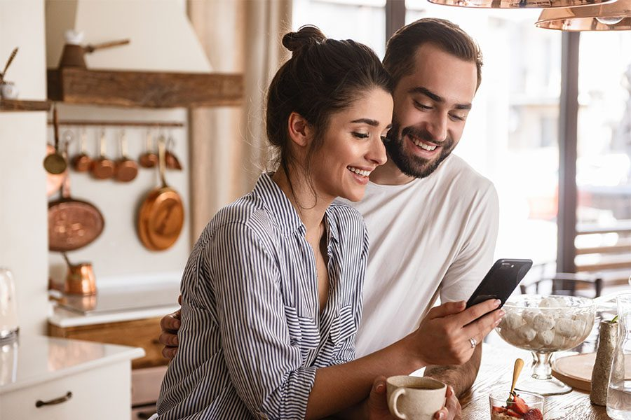 Client Center - Happy Young Couple Standing in Kitchen Using Their Phone