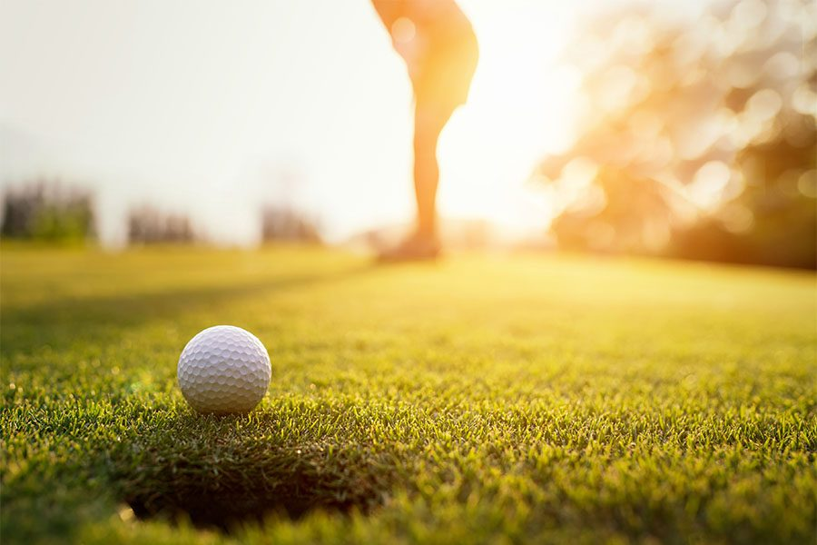 Specialized Business Insurance - View of a Golf Ball Going into Hole on a Golf Course at Sunset