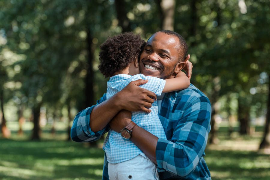 Contact Us New Hampshire Insurance - Father and Son Embracing in a Sunny Park in Summertime
