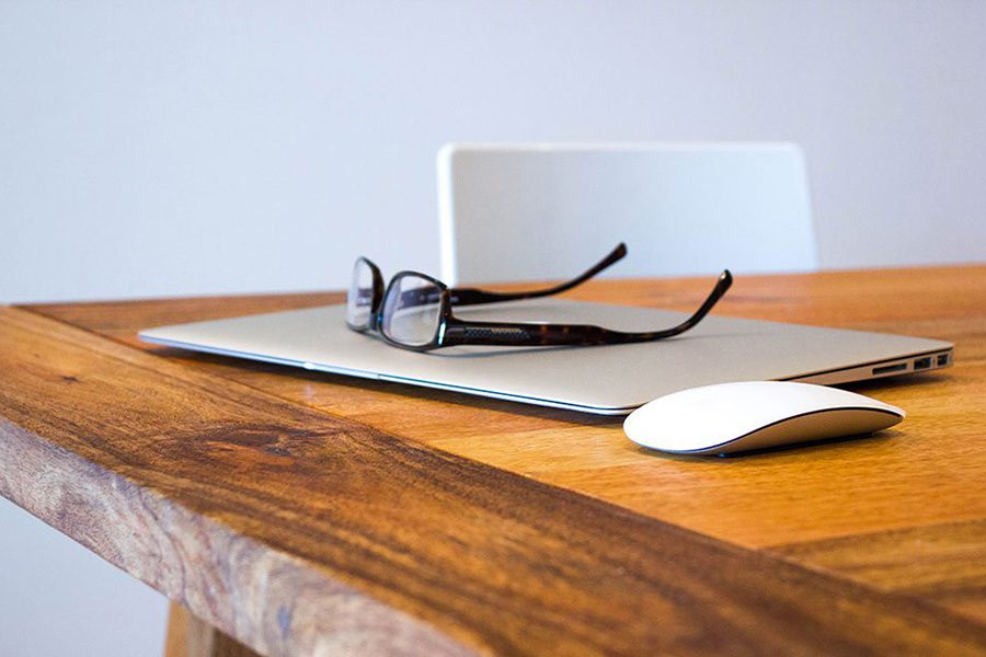 Blog - View of Laptop Mouse and Glasses Sitting on Wooden Desk