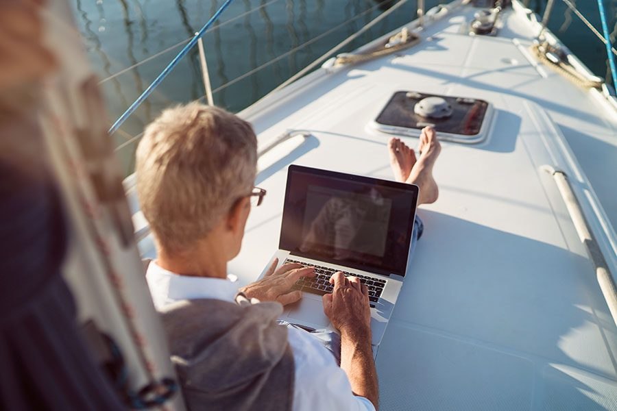 Insurance Quote - View of Mature Man Sitting on a Sailboat Using a Laptop