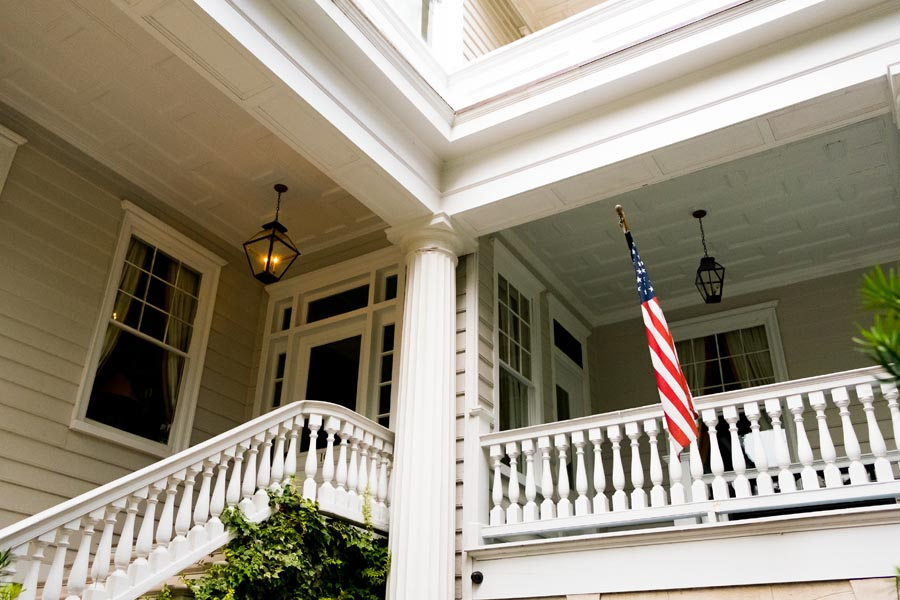 About Our Agency - Front Porch of a Home With an American Flag Hanging Outside