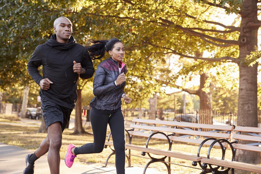 Employee Benefits - Husband and Wife Running in the Park in the Early Morning