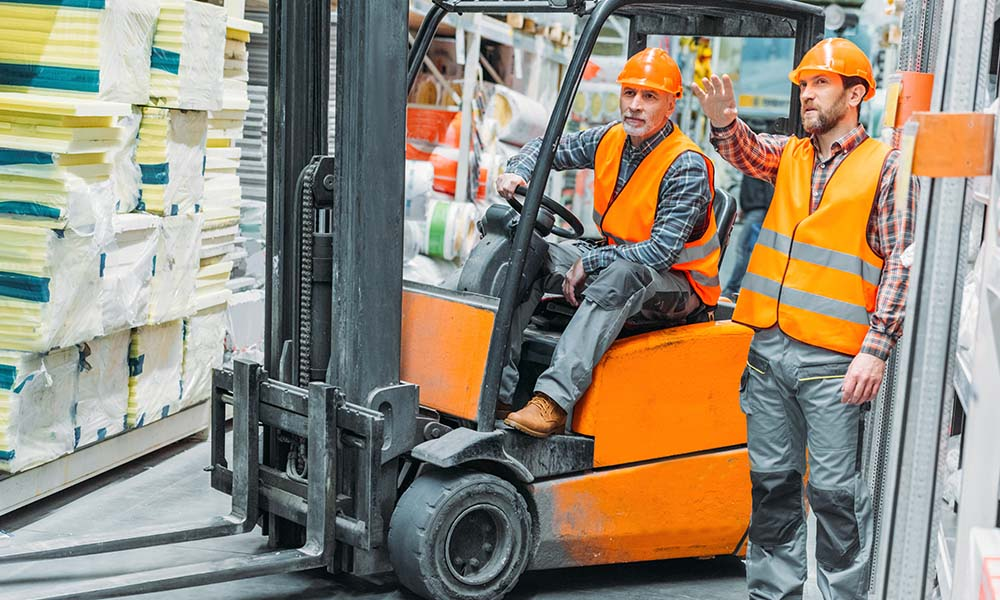 Blog - Warehouse Worker Sitting on Forklift While Talking with Another Warehouse Worker