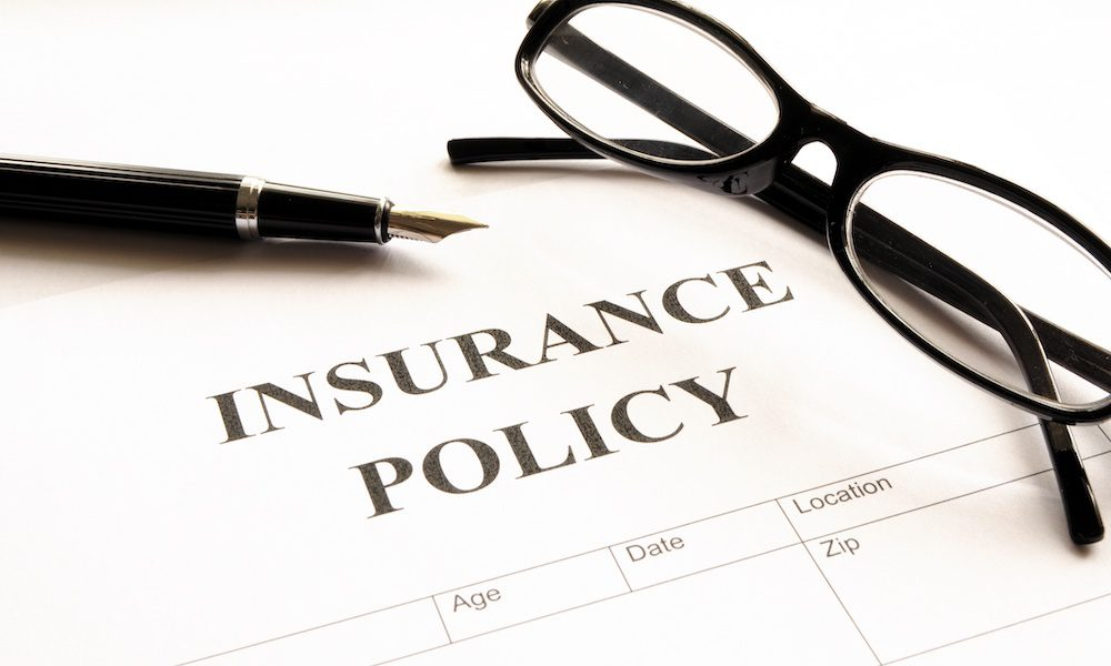 insurance policy paper with a pen and glasses on top