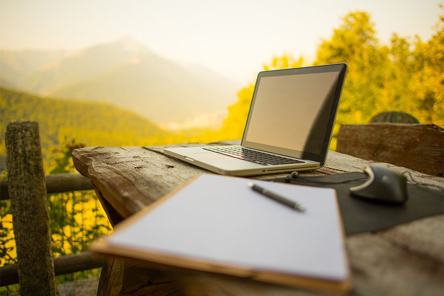 News - View of Laptop and Notebook on Wooden Table Outside
