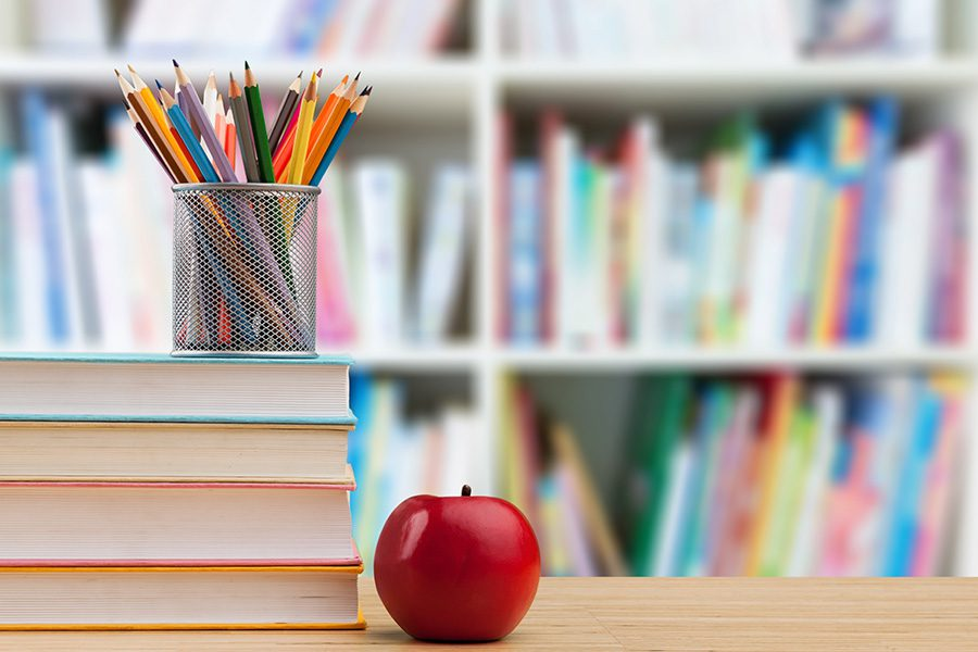 Private Schools - School Supplies And A Teachers Apple On A Desk