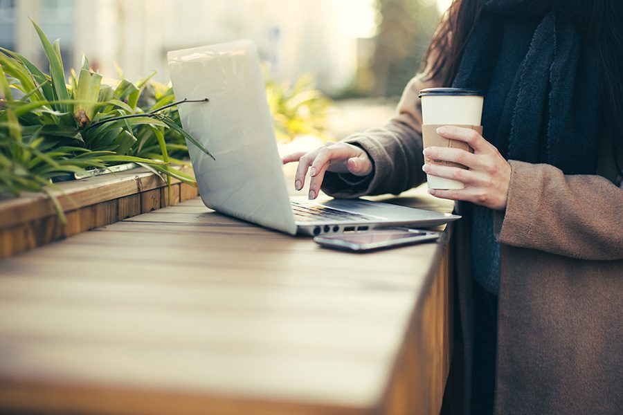 Blog - Woman Typing on Computer While Holding Coffee Outside