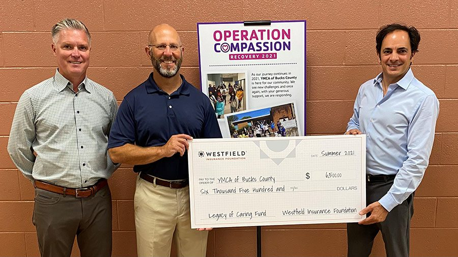 News - Community - GMG Holding a Donation Check For YMCA