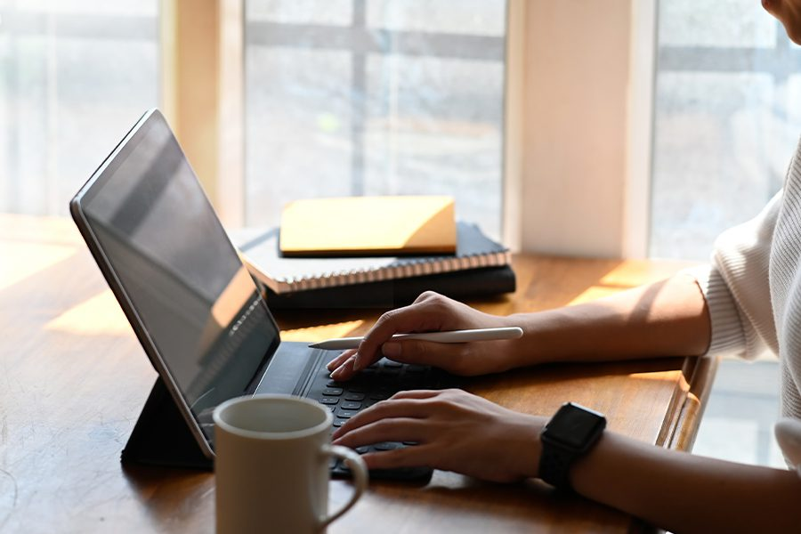 Client center - Cropped View of Woman on a Digital Tablet computer in Her Home Office