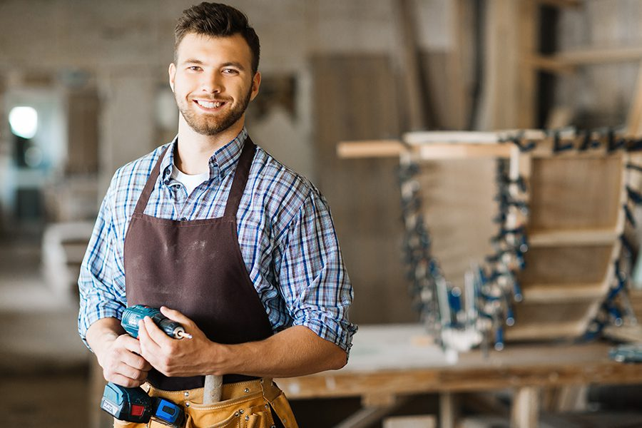 Specialized Business Insurance - Portrait of Craftsman with Drill Standing in a Spacious Workshop