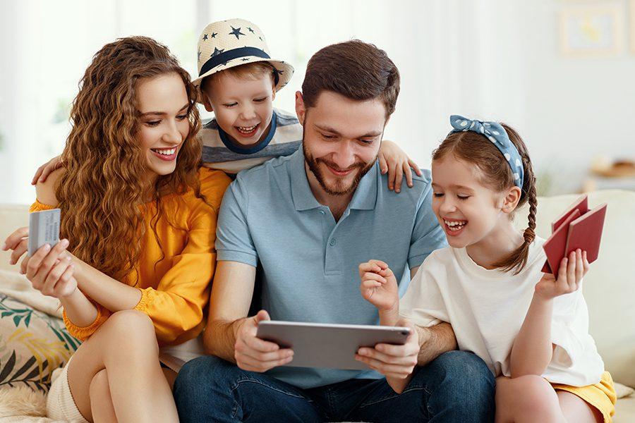 Client Center - Smiling Parents with Kids on Sofa Using a Tablet
