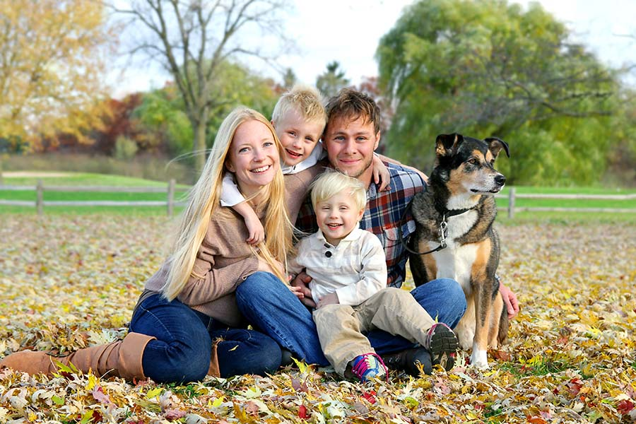 Blog - Happy Family Sitting In Field Of Leaves With Their Dog