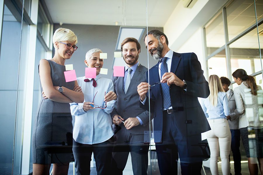 Business Insurance - Group Of Employees Looking At Glass Wall With Sticky Notes