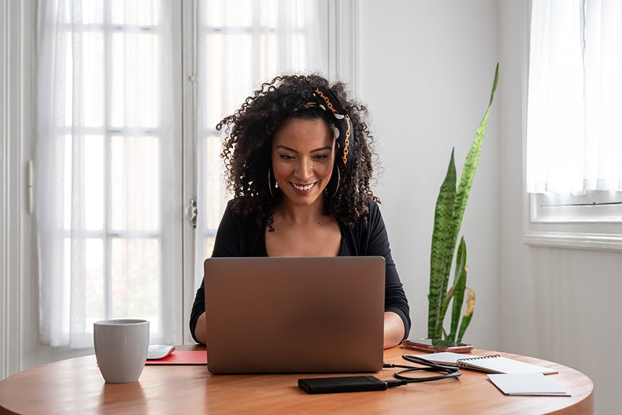 Blog - Woman Working At Her Table With Coffee On Her Computer Smiling