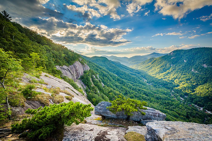 About - Scenic Green Mountains with Sun Rays and Blue Sky