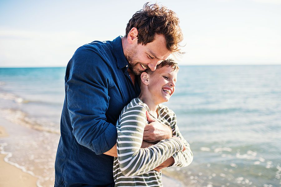 Personal Insurance - Father and Son Hugging by the Beach