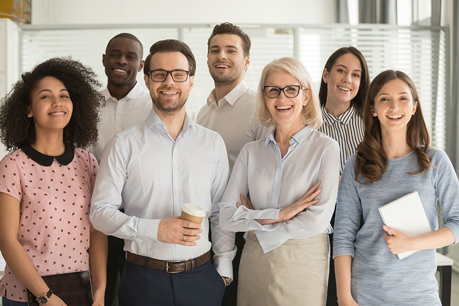 Employee Benefits - Portrait Of Happy Employees Standing In Office