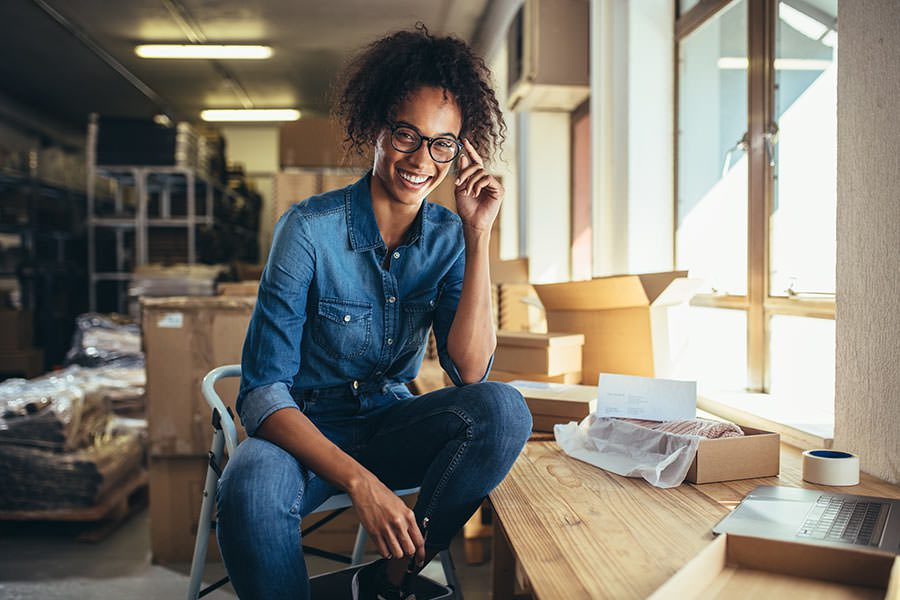 Business Insurance - African American Woman in Office Sitting and Smiling