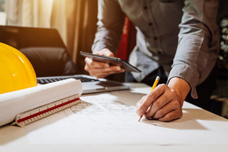 Specialized Business Insurance - Contractor Writing on Papers on Desk with Hard Hat