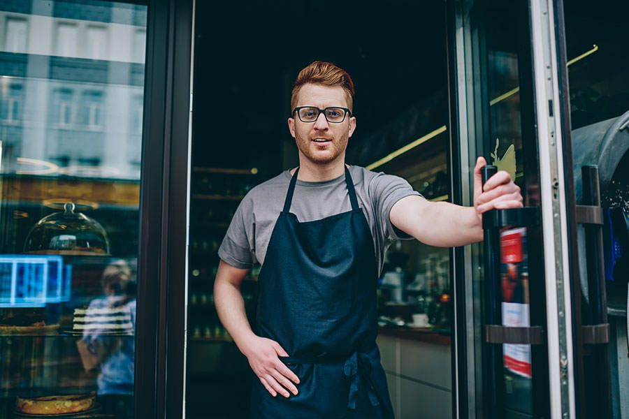 Business Insurance - Cafe Business Man Owner Wearing an Apron Holding Open Door to Cafe