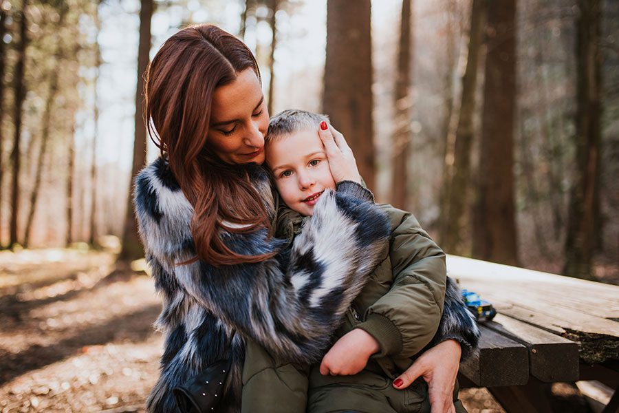 Personal Insurance - Young Mom Hugging Son in Forest