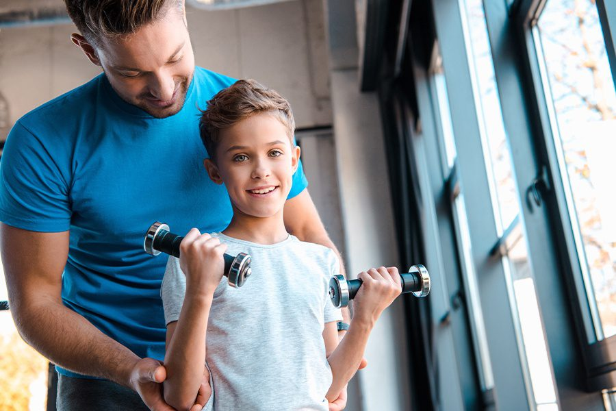Employee Benefits - Happy Father Looking at Son with Dumbbells
