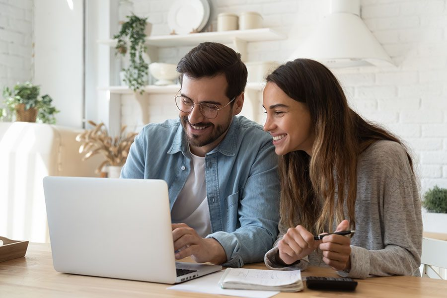 Blog - Smiling Young Couple Sitting At Home Looking At Their Laptop