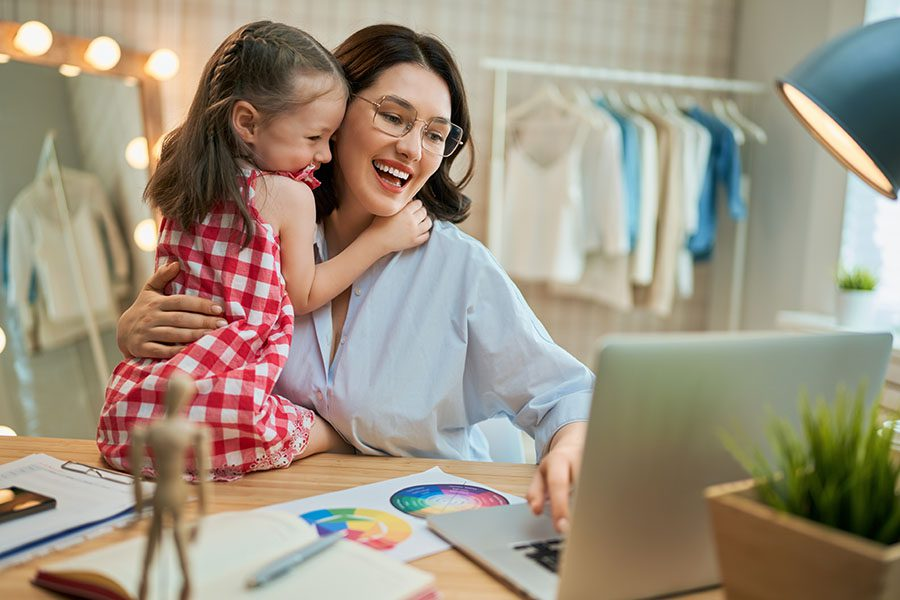 Business Insurance - Smiling Small Business Owner Working On Her Laptop While Hugging Her Daughter