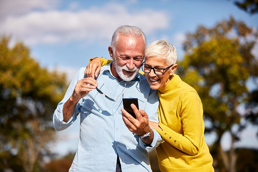 Client Center - Happy Elderly Couple Outside Looking At Their Phone