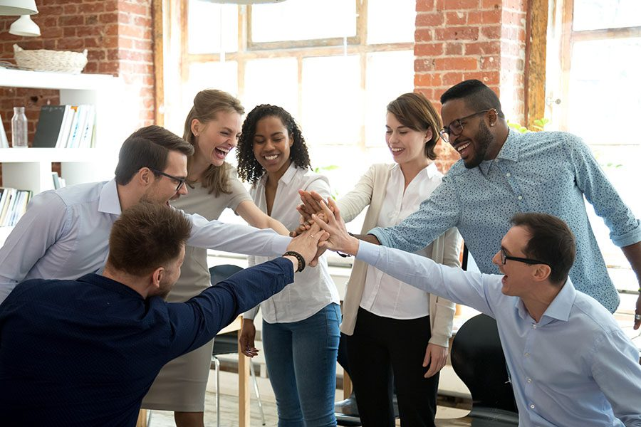 Employee Benefits - Group Of Employees Joining Their Hands Together During Meeting In The Office